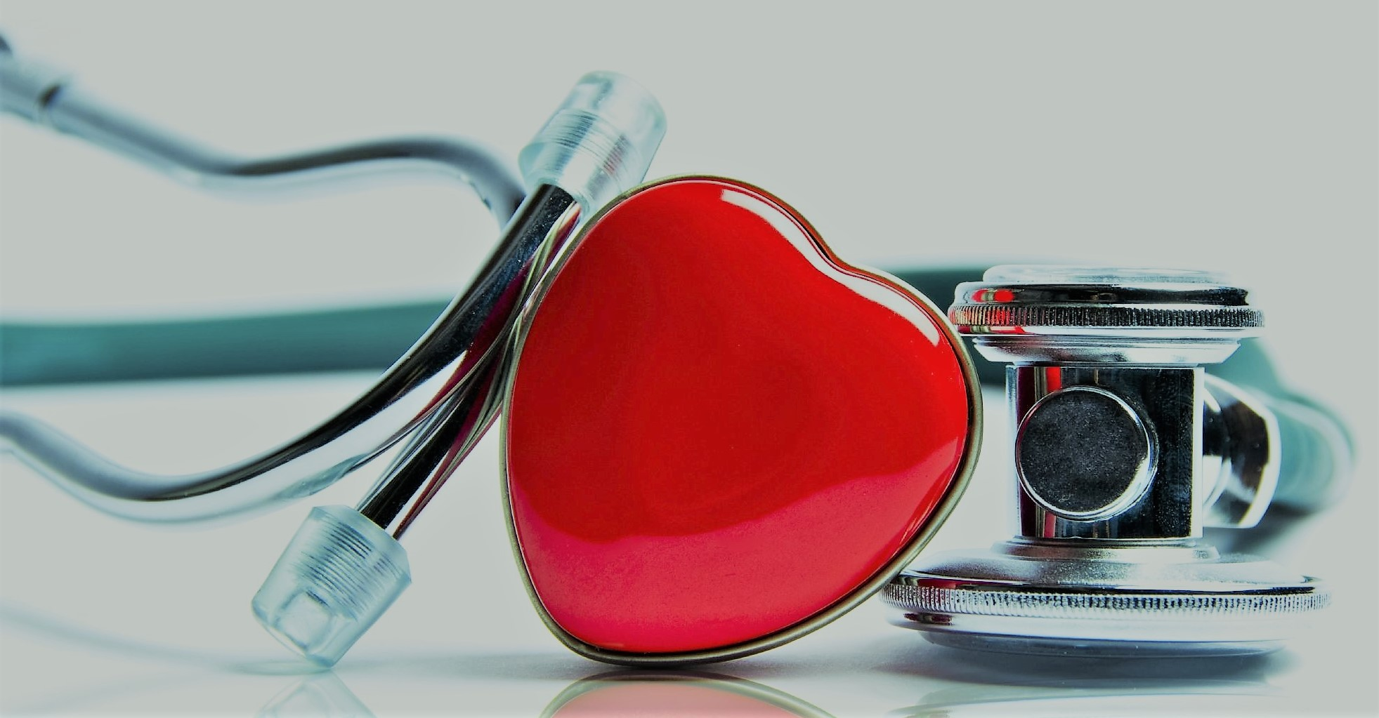 A red, plastic heart in the center of the photograph with a doctor's stethoscope leaning up against it and wrapping around.