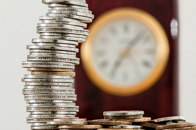 A stack of coins sits in the forefront, and in the background is a blurred clock hanging on a wall.