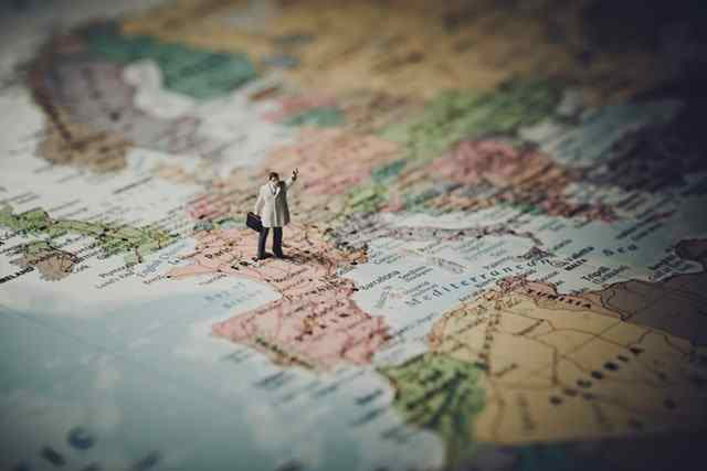 Small toy businessman stands on map of the world in Europe