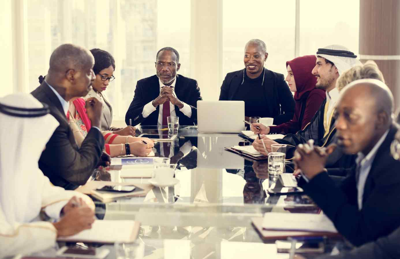 Persons of various cultures doing business around a conference table.